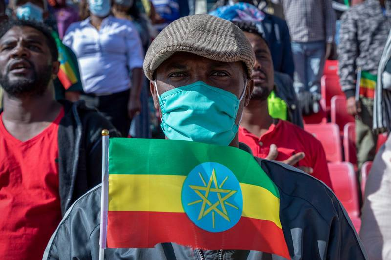 A man holds a national flag as he waits in the stands to give blood at a blood drive in support of the country's military, at a stadium in the capital Addis Ababa, Ethiopia Thursday, Nov. 12, 2020. Rallies occurred in multiple cities in support of the federal government's military offensive against the Tigray regional government, the Tigray People's Liberation Front. (AP Photo/Mulugeta Ayene)