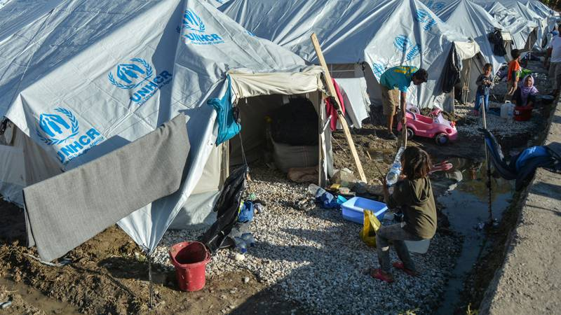 Migrants clean their tents after a rainstorm at the Kara Tepe refugee camp, on the northeastern Aegean island of Lesbos, Greece, Wednesday, Oct. 14, 2020. Around 7,600 refugees and migrants have settled at the new tent city after successive fires on Sept. 9, devastated the Moria refugee camp, making thousands of inhabitants homeless during a COVD-19 lockdown.  (AP Photo/Panagiotis Balaskas)
