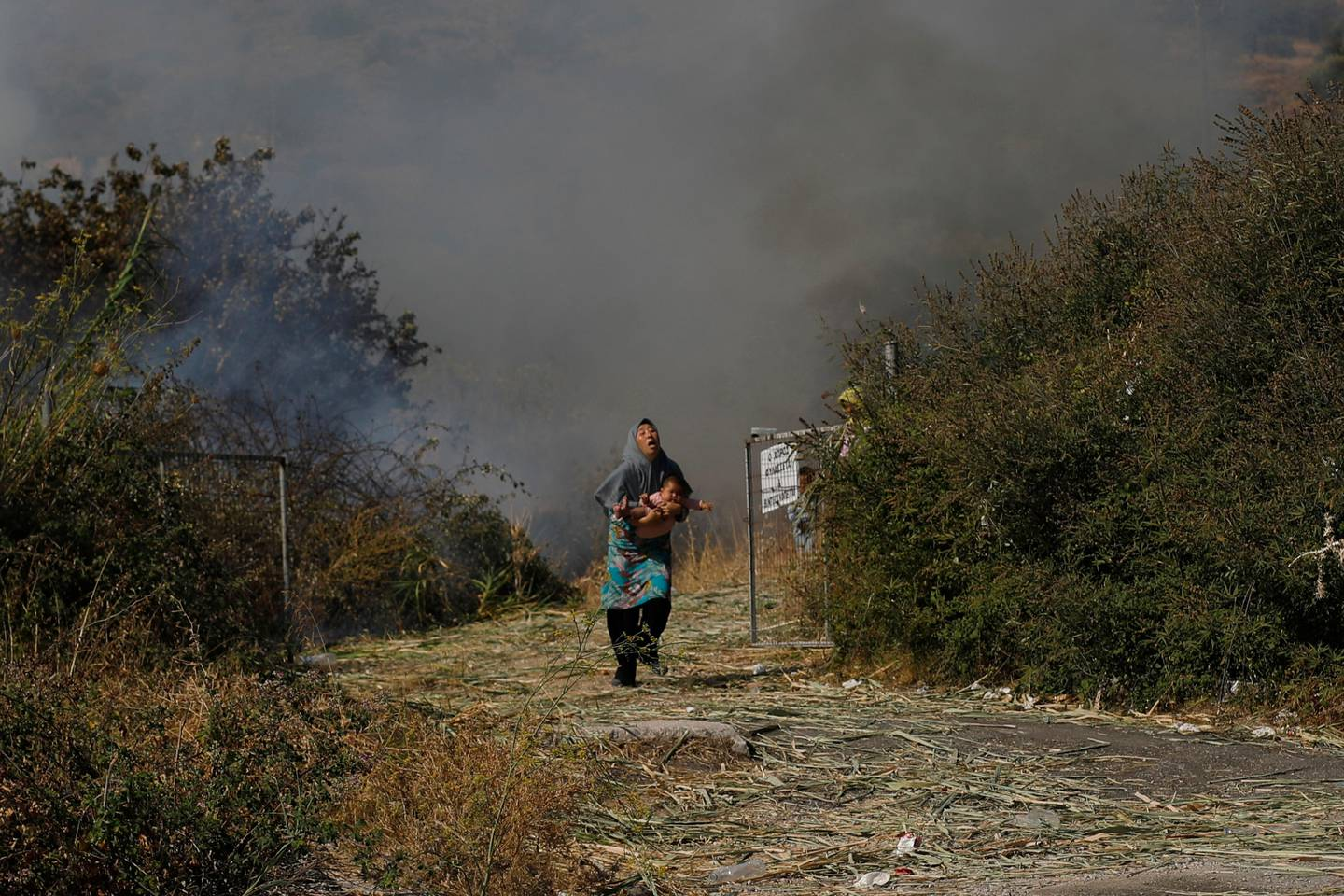 A migrant holds her baby as she runs to avoid a small fire in a field near Mytilene town, on the northeastern island of Lesbos, Greece, Saturday, Sept. 12, 2020. Greek authorities have been scrambling to find a way to house more than 12,000 people left in need of emergency shelter on the island after the fires deliberately set on Tuesday and Wednesday night gutted the Moria refugee camp. (AP Photo/Petros Giannakouris)