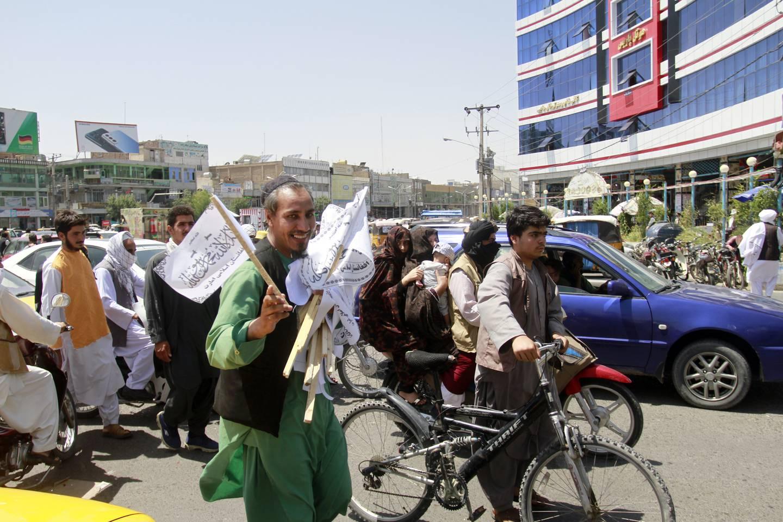 En mann deler ut Taliban-flagg i gatene i Herat for å feire at Taliban har tatt kontroll over store deler av Afghanistan og søndag var i forhandlinger om en maktoverføring. Foto: Hamed Sarfarazi / AP / NTB