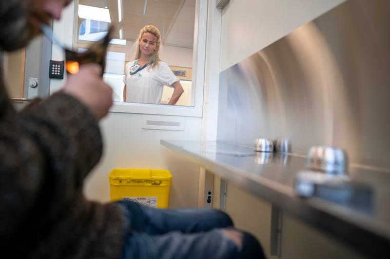 Oslo 20200831.  Christina Lidberg, fagansvarlig sykepleier, følge med når rusavhengige «Calle» (41) røyker heroin i et eget inhaleringsrom som også kalles heroinrøykerommmet. Det ligger vegg i vegg med sprøyterommet i Prindsen mottakssenter i Storgata. Foto: Heiko Junge / NTB scanpix
