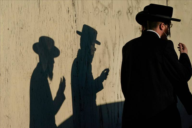 Men walk past the Yetev Lev temple Monday, Nov. 23, 2020, in the Brooklyn borough of New York. Compliance with coronavirus restrictions in some of New York's Orthodox Jewish communities has been an issue since the pandemic started last spring. (AP Photo/Frank Franklin II)