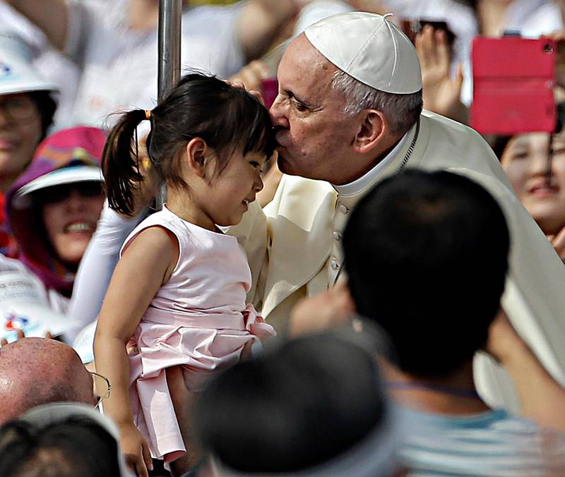 Pope Francis, right, kisses a girl as he arrives with the popemobile to celebrate a mass and the beatification Paul Yun ji-Chung and 123 martyr companions at Gwanghwamun Gate in Seoul, South Korea, Saturday, Aug. 16, 2014. Paul Yun Ji-Chung, born in 1759,  was among the earliest Catholics on the Korean Peninsula. (AP Photo/Gregorio Borgia) / TT / kod 436