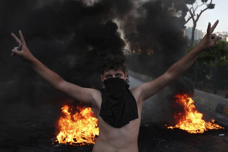 A protester flashes the victory sign, as others burn tires to block a road, in Beirut, Lebanon, Thursday, June 24, 2021. Dozens of angry protesters, angered by deteriorating living conditions and government inaction, partially blocked Beirut's main highway to the capital's only airport, turning trash bin over and setting tires on fire. (AP Photo/Bilal Hussein)