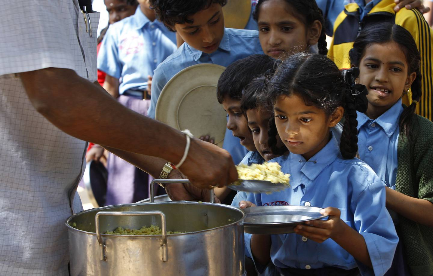 A girl looks at food served to her for free at a government-run school in Bangalore, India, Wednesday, Jan. 11, 2012. UNICEF's latest data say one-third of the world's malnourished children younger than 3 lives in India, a rate worse than sub-Saharan Africa. Indian Prime Minister Manmohan Singh has called child malnutrition the country's shame. (AP Photo/Aijaz Rahi)