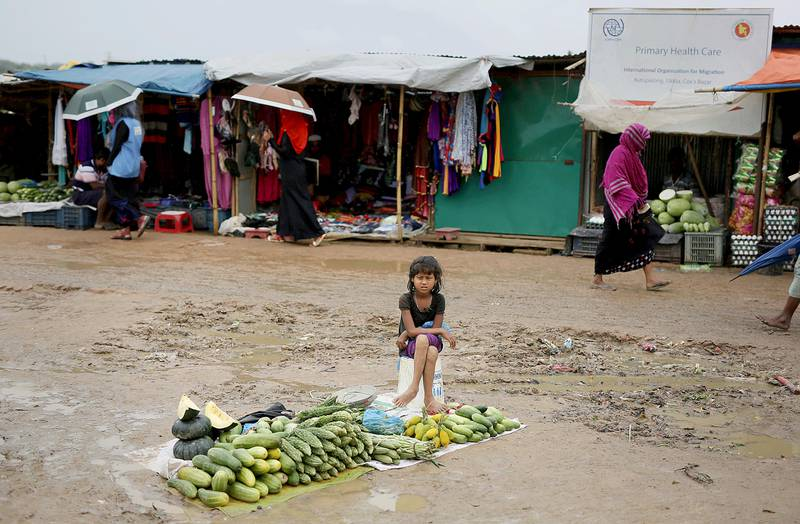 In this Aug. 28, 2018, photo, a Rohingya refugee girl sells vegetables in Kutupalong refugee camp, Bangladesh.  More than half a million Rohingya children live in the congested camps. They rely on 1,200 learning centers set up by aid organizations that can?ƒÙt accommodate everyone and only offer classes up to a 5th-grade level. Most Rohingya girls are expected to get married by the age of 16, and sometimes as early as 14. (AP Photo/Altaf Qadri)