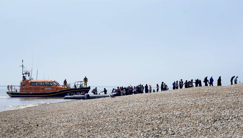 People thought to be migrants are watched over by the RNLI as they make their way up the beach after arriving on a small boat at Dungeness in Kent, England, Monday July 19, 2021. They were later taken away by Border Force staff. (Gareth Fuller/PA via AP)