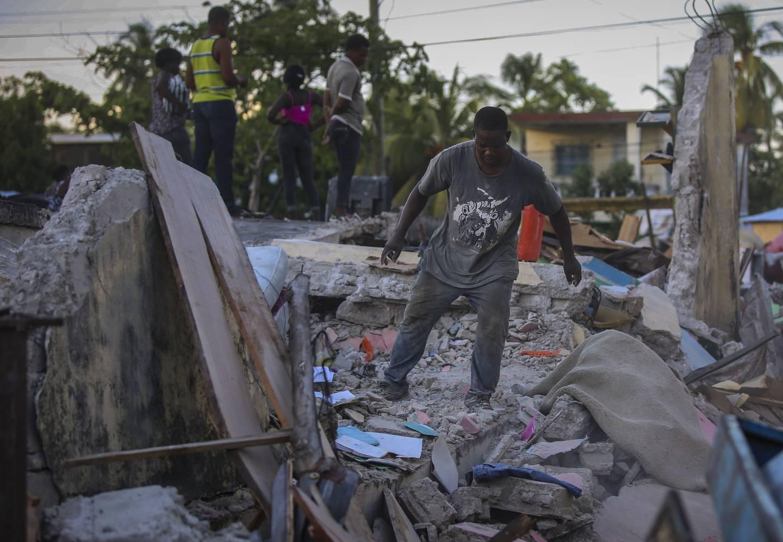 En mann prøver å redde eiendeler fra sitt sammenraste hus i Les Cayes i Haiti. Foto: Joseph Odelyn / AP / NTB