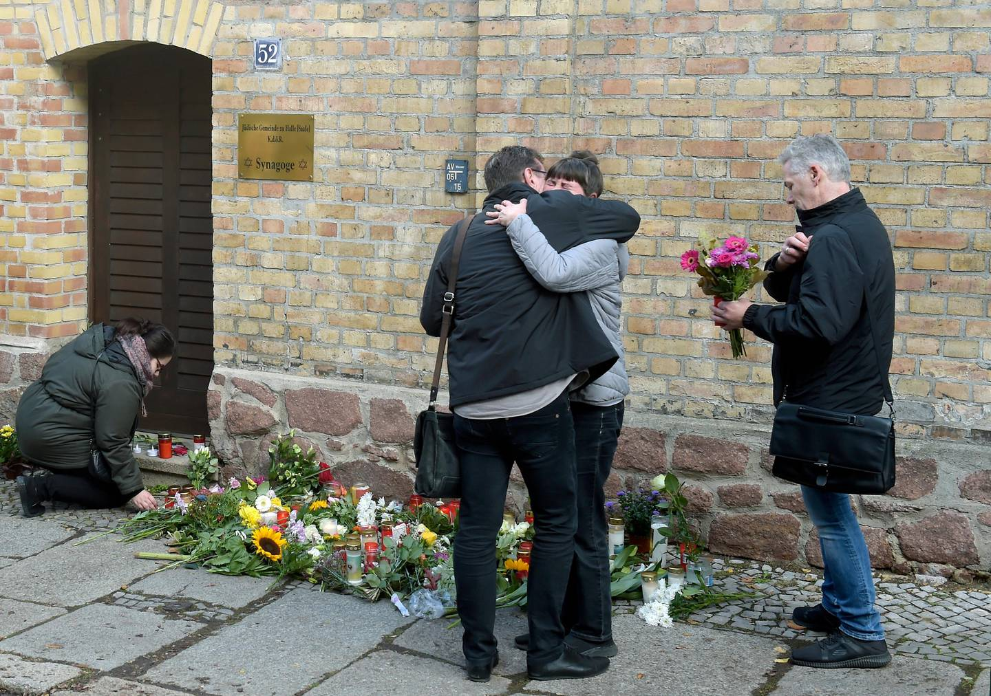 People mourn in front of a synagogue in Halle, Germany, Thursday, Oct. 10, 2019. A heavily armed assailant ranting about Jews tried to force his way into a synagogue in Germany on Yom Kippur, Judaism's holiest day, then shot two people to death nearby in an attack Wednesday that was livestreamed on a popular gaming site. (AP Photo/Jens Meyer)