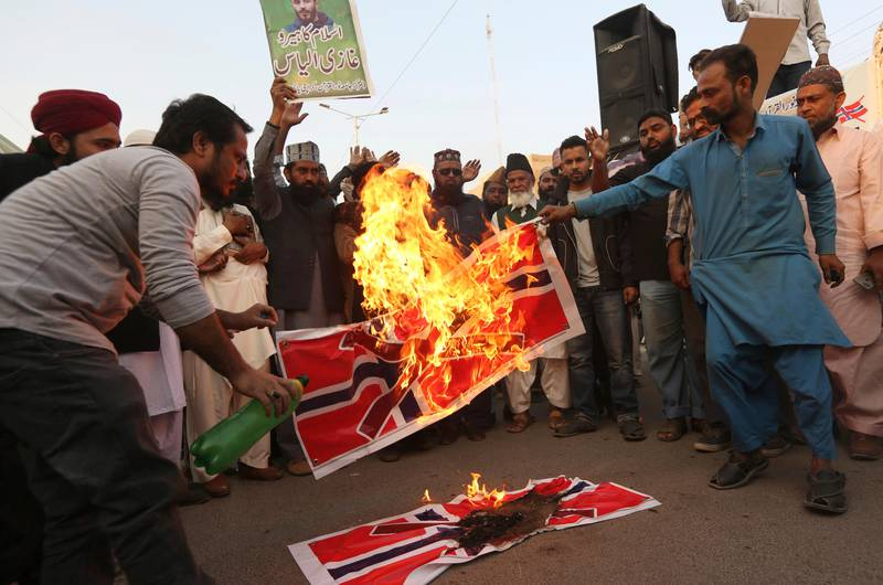 Pakistani protesters burn representations of Norwegian flag to condemn the desecration of the Muslim Holy book Quran in the Norwegian city of Kristiansand, in Karachi, Pakistan, Tuesday, Nov. 26, 2019. Pakistan's Foreign Ministry said Saturday it had summoned Norway's ambassador to convey the deep concern of the government and Pakistani people over the recent burning of the Quran by a Norwegian man that was caught on video. (AP Photo/Fareed Khan)