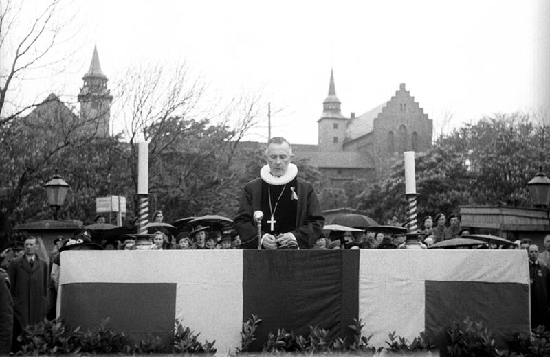 OSLO 19450517 Fredsdagene 1945. 17 mai gudstjeneste utendørs på Akershus festning. Biskop Eivind Berggrav forettet. Norsk flagg på alteret, festningeni bakgrunnen. Regnvær. Foto: NTB / Scanpix