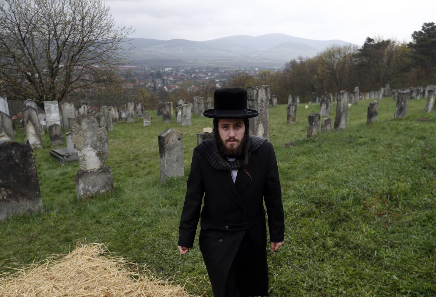 Hasidic Jewish pilgrims walk to the grave of Grand Rabbi Yeshaya Steiner, founder of a famous Hasidic dynasty, to commemorate the anniversary of his day of death in the village of Bodrogkeresztur, Hungary, Thursday, April 15, 2021. Despite many government imposed restrictions in place in Hungary to prevent the spread of the coronavirus, religious events may still be held. AP Photo/Laszlo Balogh