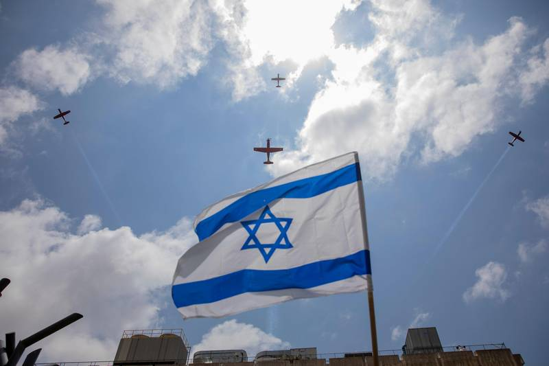 An Israeli flag waves as an Air Force aerobatic team flies in formation over the The Hillel Yaffe Medical Center, during a lockdown following government measures to help stop the spread of the coronavirus, on Israel's 72nd Independence Day, in the northern Israeli city of Hadera, Israel, Wednesday, April 29, 2020.(AP Photo/Ariel Schalit)