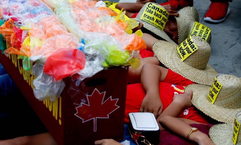 With a mock container loaded with garbage, environmentalists stage a die-in protest outside the Canadian Embassy to demand the Canadian government to speed up the removal of several containers of garbage that were shipped to the country Tuesday, May 21, 2019, in Manila, Philippines. The Philippines recalled its ambassador and consuls in Canada last week over Ottawa's failure to comply with a deadline to take back 69 containers of garbage that Filipino officials say were illegally shipped to the Philippines years ago. (AP Photo/Bullit Marquez)