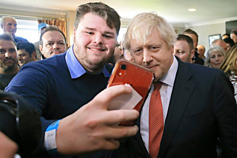 Britain's Prime Minister Boris Johnson poses for a selfie with a supporter, during a visit to Sedgefield Cricket Club in County Durham, north east England, Saturday Dec. 14, 2019, following his Conservative party's general election victory.  Johnson called on Britons to put years of bitter divisions over the country's EU membership behind them as he vowed to use his resounding election victory to finally deliver Brexit. (Lindsey Parnaby/Pool via AP)