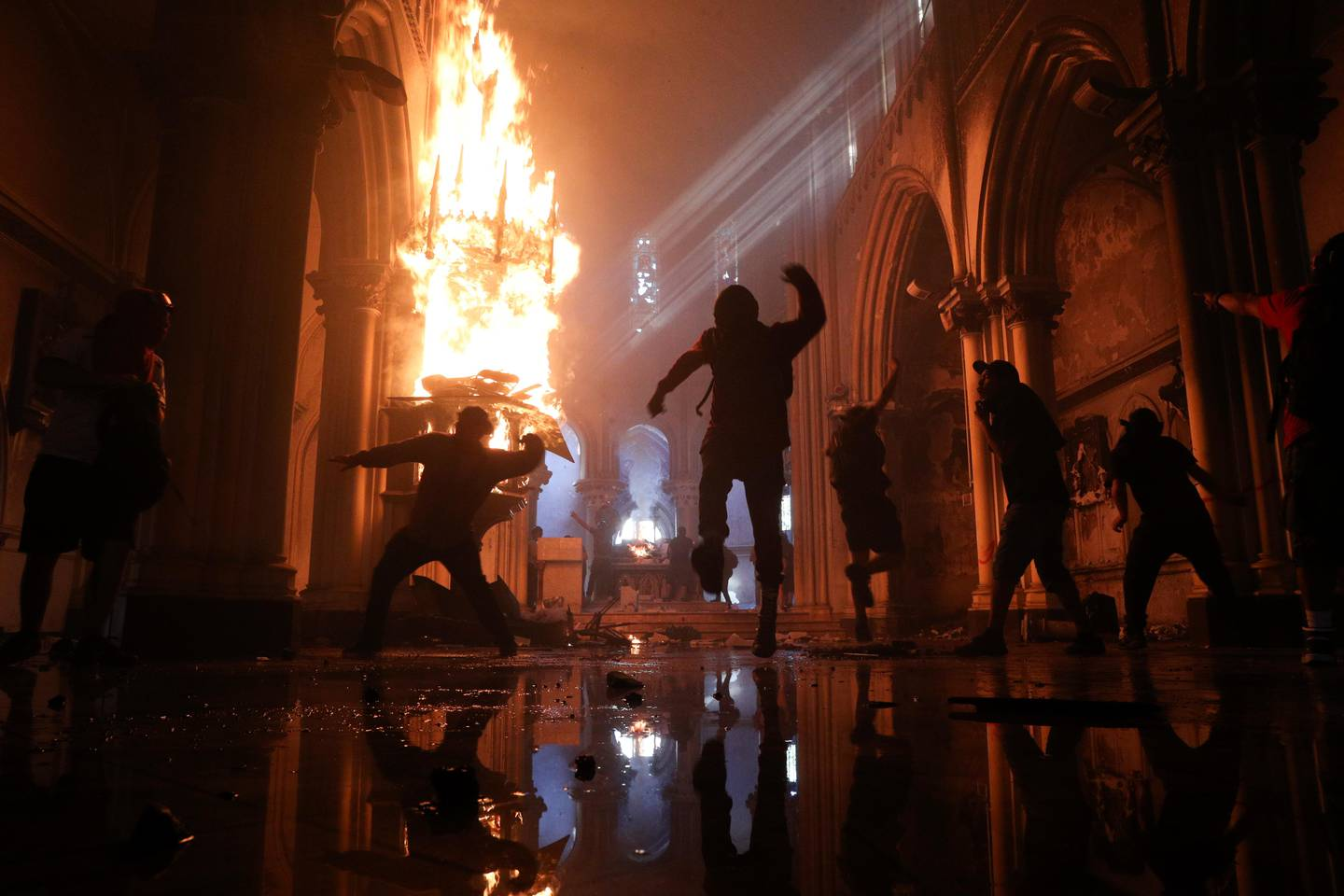 Protesters storm the San Francisco de Borja church, that belongs to Carabineros, Chile's national police force, on the one-year anniversary of the start of anti-government mass protests over inequality in Santiago, Chile, Sunday, Oct. 18, 2020.  (AP Photo/Esteban Felt)