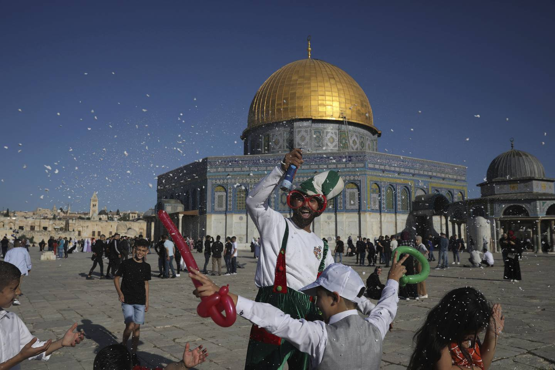 En klovn sprayer barn med skum mens muslimer samles til Eid al-Fitr-bønnen ved  Al-Aqsa-moskeen i gamlebyen i Jerusalem, torsdag 13. mai 2021.