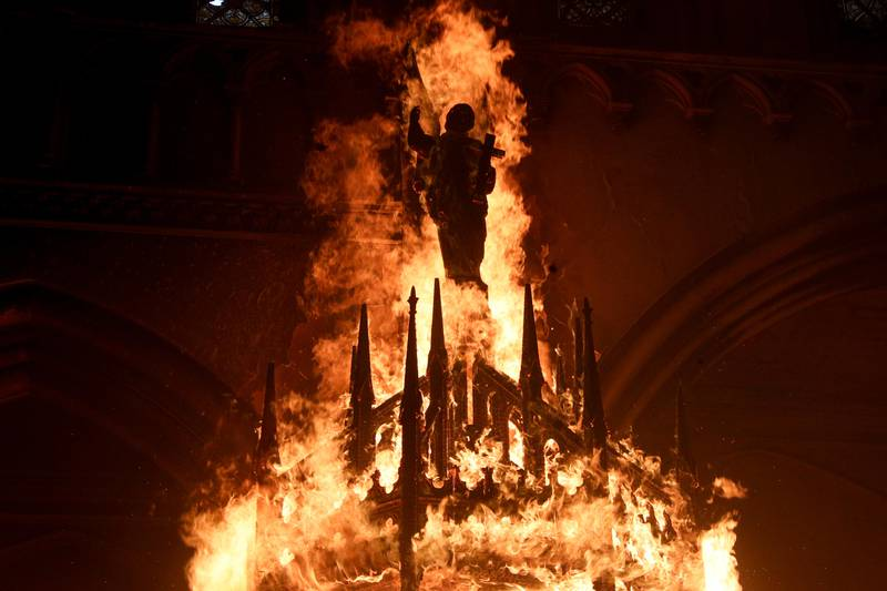 A saint figure burns after protesters storm the San Francisco de Borja church, that belongs to Carabineros, Chile's national police force, on the one-year anniversary of the start of anti-government mass protests over inequality in Santiago, Chile, Sunday, Oct. 18, 2020. (AP Photo/Esteban Felix)