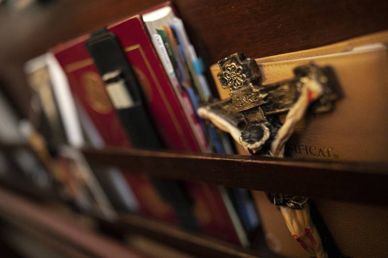 A crucifix is set beside books in a pew at St. Charles Borromeo Seminary in Wynnewood, Pa., on Wednesday, Feb. 5, 2020. Soaring chapels at the seminary vibrate with blasts of organs during Mass. (AP Photo/Wong Maye-E)