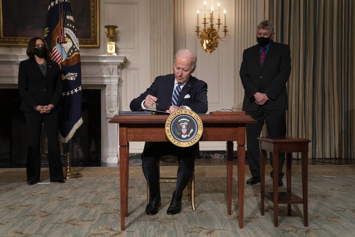 Vice President Kamala Harris, left, and White House science adviser Dr. Eric Lander, right, look on as President Joe Biden signs a series of executive orders on climate change, in the State Dining Room of the White House, Wednesday, Jan. 27, 2021, in Washington. (AP Photo/Evan Vucci)