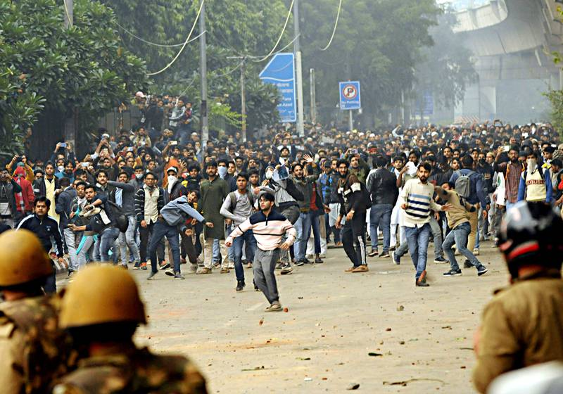 Students shout slogans and pelt stones outside the Jamia Millia Islamia University during a protest against the Citizenship Amendment Bill, in New Delhi, India, Friday, Dec. 13, 2019. Japanese Prime Minister Shinzo Abe is postponing a meeting with Prime Minister Narendra Modi in India's northeast. The region has been the site of continuing protests against a new law that grants citizenship to non-Muslims who migrated from neighboring countries. (AP Photo)