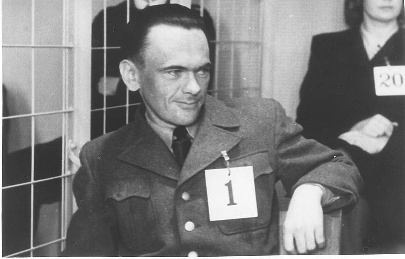 """Henry Oliver Rinnan, (1915-1947) var en av de verste og mest beryktede norske krigsforbrytere under den annen verdenskrig 1940-45. Rinnanbanden (kallt """"Sonderabteilung Lola"""") ga seg ut for å være norske motstandsfolk og innfiltrerte seg i organiserte norske motstandsgrupper. Noe som resulterte i at flere hundre nordmenn ble torturert og minst 80 ble drept.  På bildet hovedpersonen med nr.1 på brystet under rettsaken der han ble dømt for 13 mord og snere henrettet..  11 av Rinnans hjelpere ble dødsdømt, men to av ble senere benådet. FOTO; Ukjent/ Arkiv / SCANPIX"""