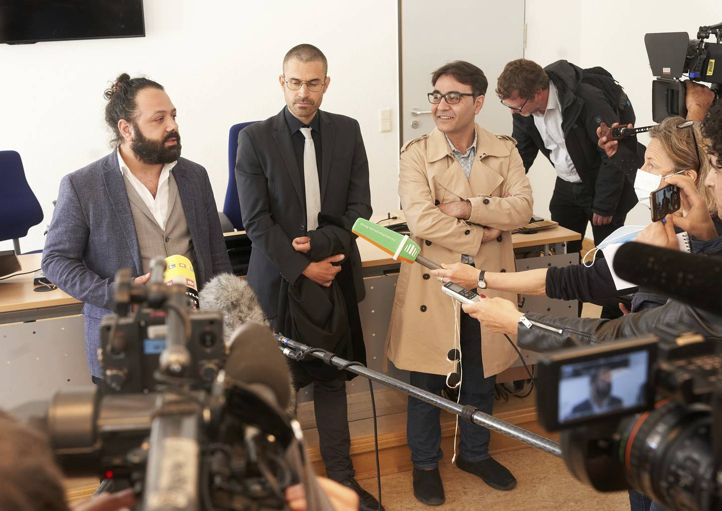 The joint plaintiffs Wassim Mukdad, from left, Patrick Kroker, attorney, and Hussein Ghrer talk to journalists after the first day's trial in Koblenz, Germany, Thursday, April 23, 2020. Two former members of Syria's secret police go on trial Thursday in Germany accused of crimes against humanity for their role in a government-run detention center where large numbers of opposition protesters were tortured.(Thomas Frey/dpa via AP)