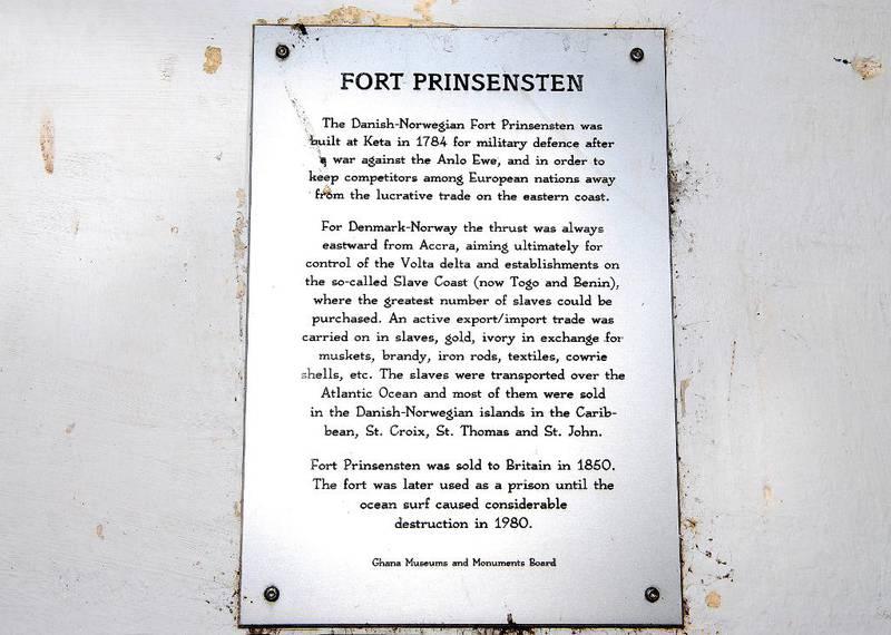 Plaketten på murveggen på fort Prinsensten fortel den dansk-norske slavehistoria i Vest-Afrika med få ord.