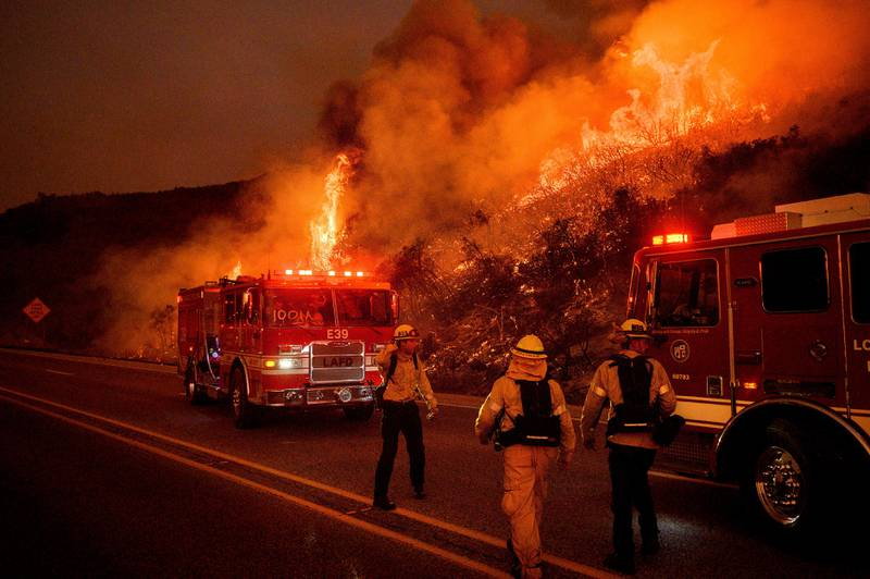 FILE - In this Nov. 26, 2019, file photo, firefighters battle the Cave Fire as it flares up along Highway 154 in the Los Padres National Forest above Santa Barbara, Calif. The outbreak of the coronavirus is making the U.S. Forest Service and others change strategies for fighting wildfires, as the need for isolation and social distancing comes into play against the necessity of having firefighters work and live closely together. (AP Photo/Noah Berger, File)