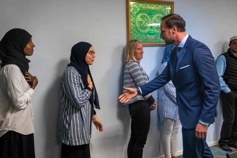 BÆRUM Kronprins Haakon hilser på Sriha da han besøker den terrorrammede moskeen Al-Noor Islamic Centre på Skui i Bærum. Blodflekker og kulehull er synlige etter skyting og basketaket da Philip Manshaus tok seg inn i moskëen. Foto: Heiko Junge / NTB scanpix