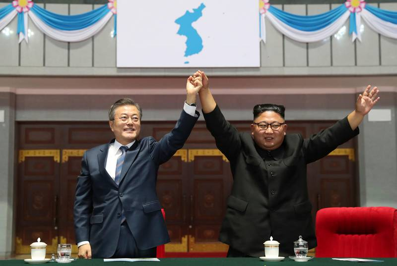 """In this Wednesday, Sept. 19, 2018, file photo, South Korean President Moon Jae-in and North Korean leader Kim Jong Un raise their hands after watching the mass games performance of """"The Glorious Country"""" at May Day Stadium in Pyongyang, North Korea. (Pyongyang Press Corps Pool via AP, File)"""