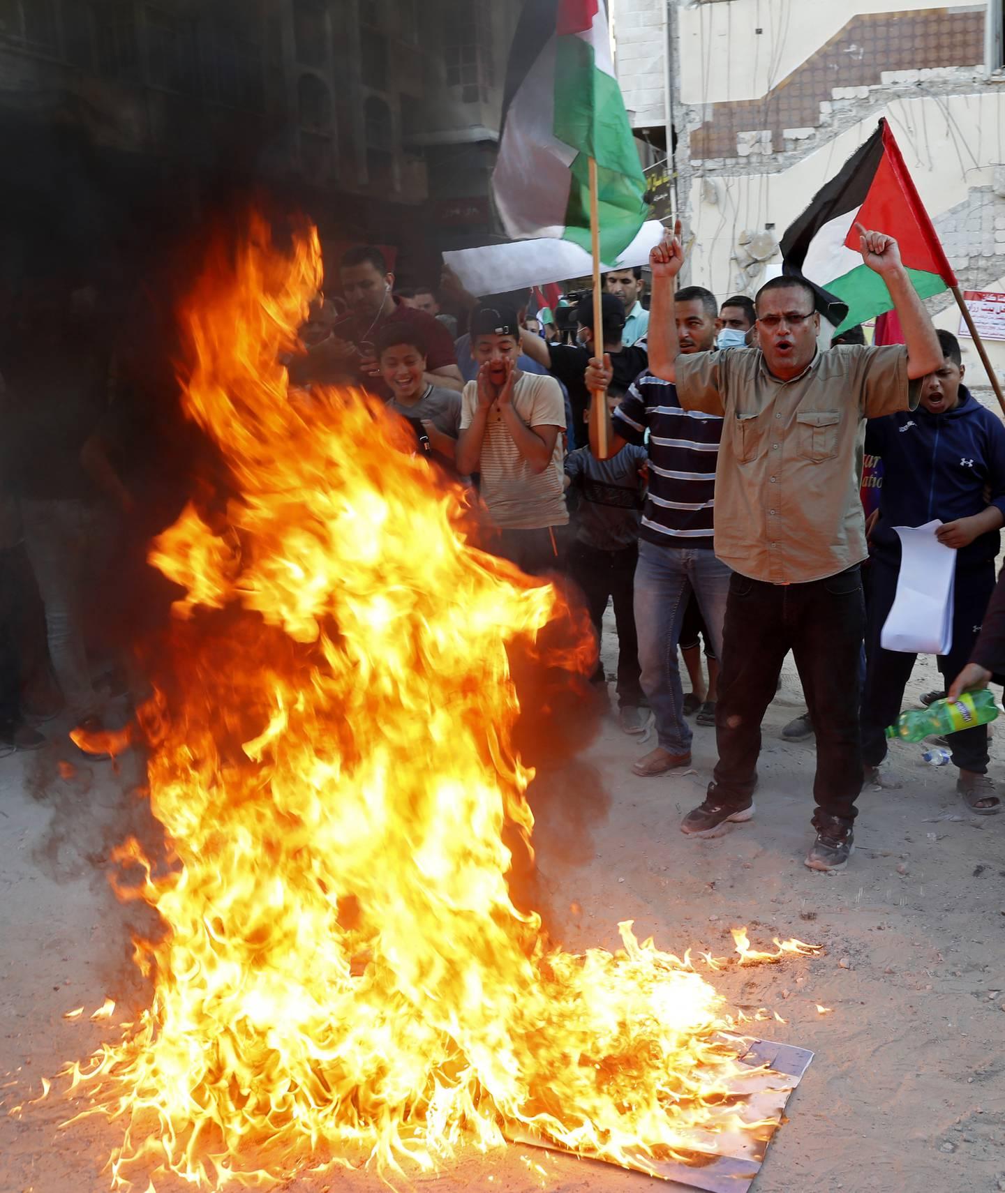 Palestinerne svarte med å brenne det israelske flagget og rope antiisraelske slagord. Foto: Adel Hana / AP / NTB