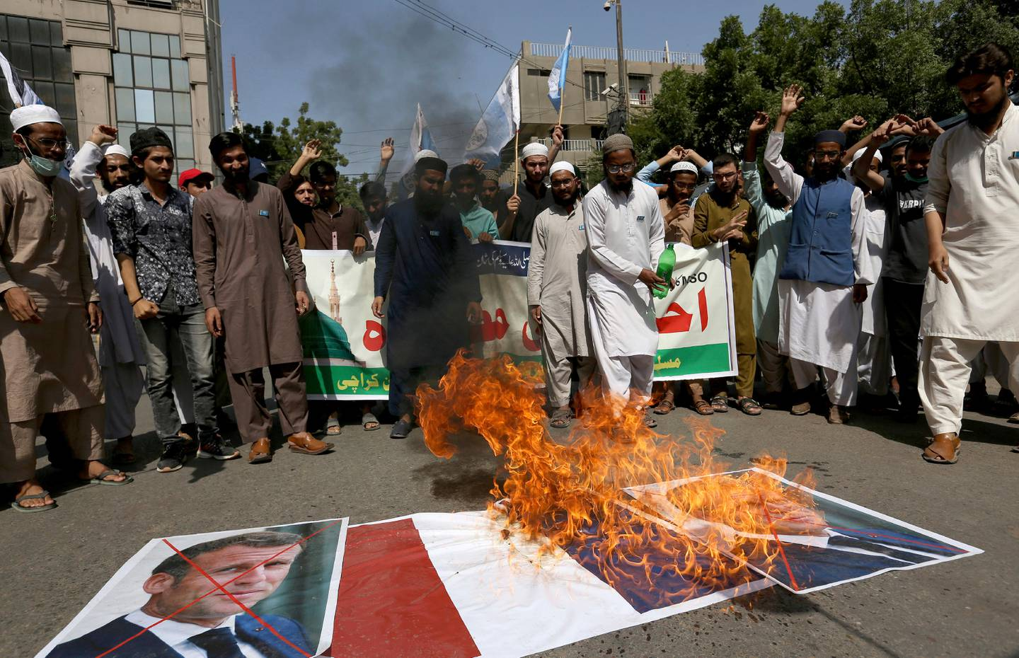 Supporters of the Muslims Students Organization burn a representation of a French national flag and defaced images of French President Emmanuel Macron during a protest against the president and against the publishing of caricatures of the Prophet Muhammad they deem blasphemous in Karachi, Pakistan, Friday, Oct. 30, 2020. Muslims have been calling for both protests and a boycott of French goods in response to France's stance on caricatures of Islam's most revered prophet. (AP Photo/Fareed Khan)