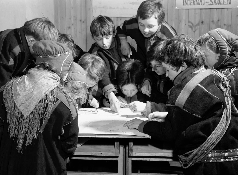 Karasjok, Finnmark, januar 1950. Fra Internatskolen for Flyttsame-barn. De samiske barna bor på internat på skolen.  Her interiør fra et klasserom, der elevene er opptatt med å tegne inn reinens flytt-ruter på kartet over Finnmark. Dette er en av de få samisk-relaterte arbeidsoppgavene, og de kaster seg over den med liv og lyst.  Foto: Sv. A. Børretzen / Aktuell / NTB