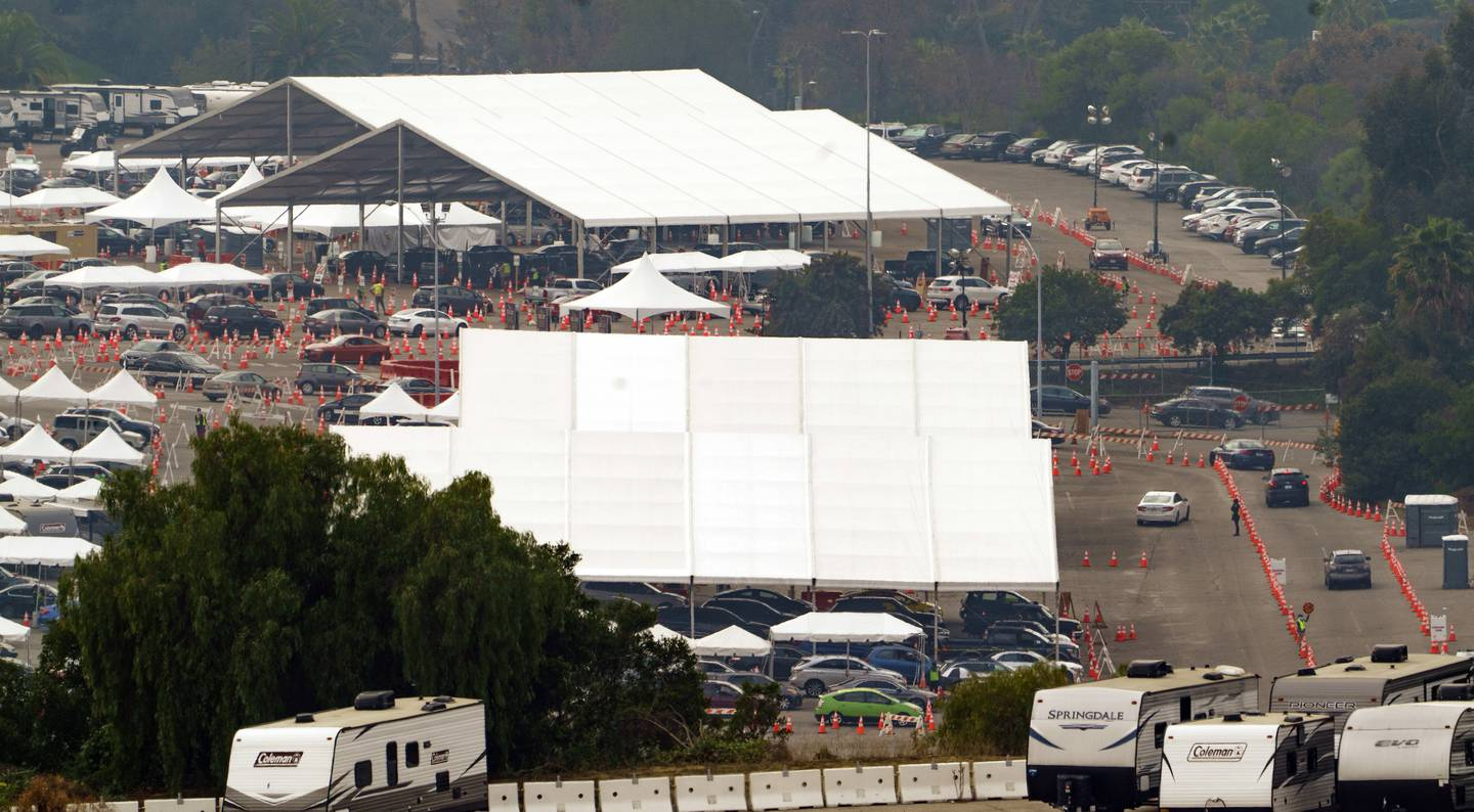 Motorists receive COVID-19 vaccines under large tents at a Los Angeles County location at Dodger Stadium in Los Angeles, Wednesday, Feb. 10, 2021. (AP Photo/Damian Dovarganes)