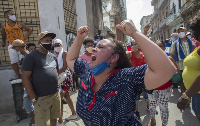 A woman shouts pro-government slogans as anti-government protesters march in Havana, Cuba, Sunday, July 11, 2021. Hundreds of demonstrators took to the streets in several cities in Cuba to protest against ongoing food shortages and high prices of foodstuffs. (AP Photo/Ismael Francisco)