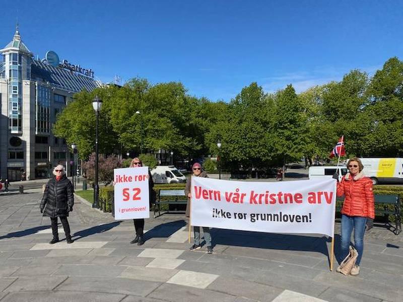 Med banner sto en liten gruppe demonstranter foran Stortinget – til kamp for fortsatt kristenarv i Grunnloven. De var til sammen ti og to av dem sa til Vårt Land at de var kommunestyremedlemmer for Frp. Frp deltok ikke i debatten.
