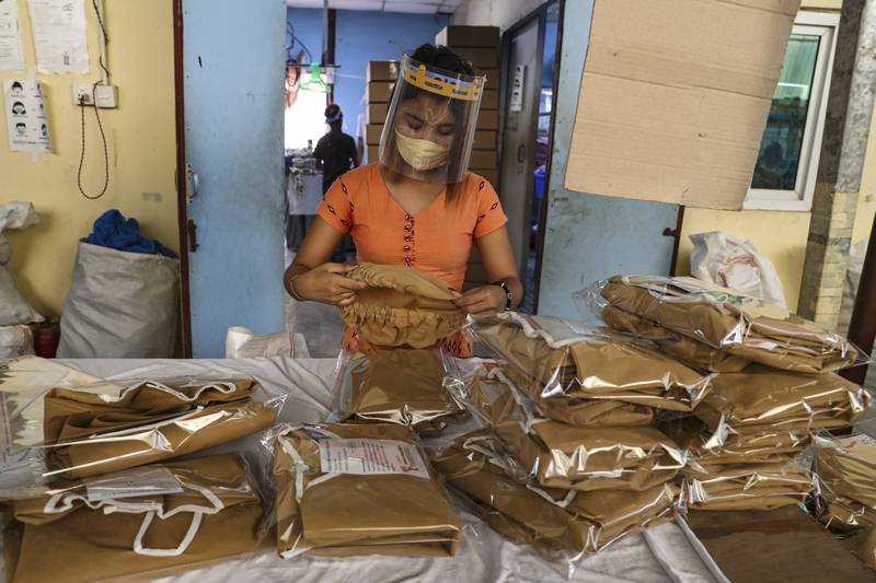 A woman wearing face mask and face shield to help curb the spread of the new coronavirus, checks surgical gown at a packing session at a garment factory Thursday, May 28, 2020, at Industrial Zone in Yangon, Myanmar. Despite a poor public health infrastructure and crowded urban areas, Myanmar has reported a surprising low number of COVID-19 cases, with just a little over 200 confirmed and a few deaths. (AP Photo/Thein Zaw)