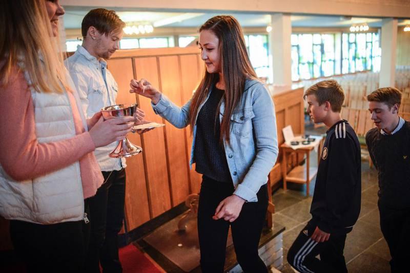 Prest Endre Olav Osnes deler ut kjeks og Anniken Baardvik Hamre held vinbegeret. Fremst i køa er Celine og Eirik.