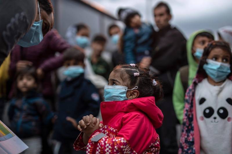 Refugees and migrants wearing masks to prevent the spread of the coronavirus, wait to get on a bus after their arrival at the port of Piraeus, near Athens, on Monday, May 4, 2020. Greek authorities are moving 400 migrants, mostly families, to the mainland to help ease overcrowded conditions at the camp Moria in Lesbos island. (AP Photo/Petros Giannakouris)