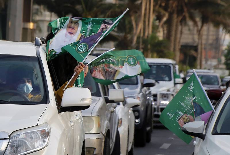 Saudis wave national flags with pictures of Saudi King Salman, right, and Crown Prince Mohammed bin Salman during celebrations marking National Day to commemorate the unification of the country as the Kingdom of Saudi Arabia, in Jiddah, Saudi Arabia, Wednesday, Sept. 23, 2020. (AP Photo/Amr Nabil)