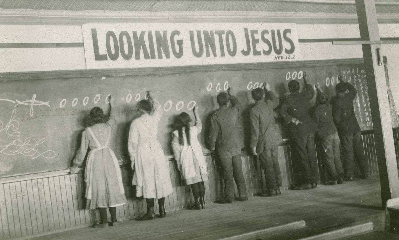 Dette bildet frå 1910 viser barn som skriv på ei tavle på Red Deer Indian Industrial School in Alberta, Canada.