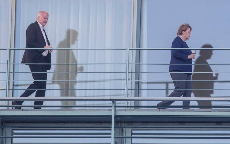 German Chancellor Angela Merkel, right, and Interior Minister Horst Seehofer stand on the balcony of the chancellery in Berlin before a meeting Saturday, June 30, 2018. (Paul Zinken/dpa via AP)