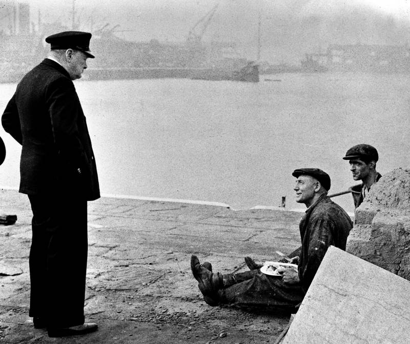 Britain's Prime Minister Winston Churchill, left, speaks to two workmen eating their lunch, in England, in September 1941, while touring a docks area. Upon seeing their well-filled plates, Churchill asked