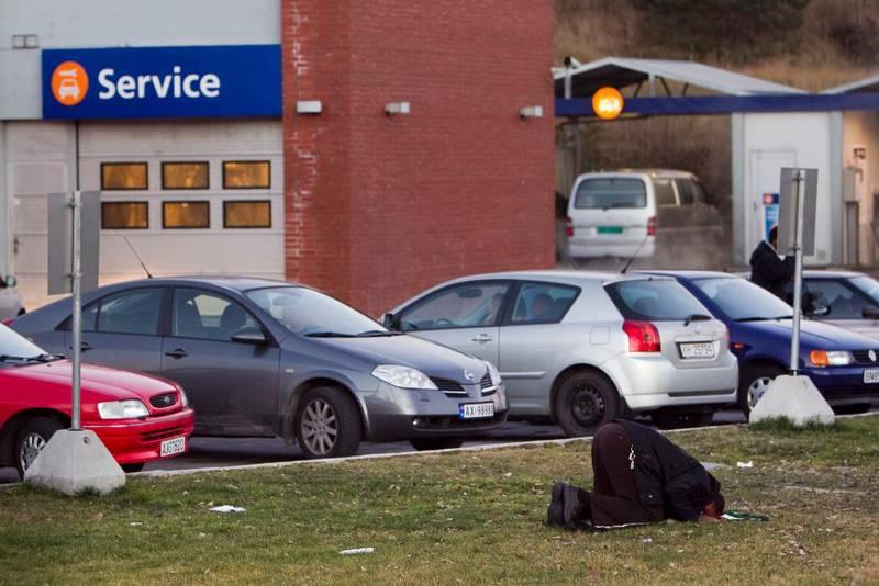 En muslim ber en aftenbønn på gresset ved en bensinstasjon ved Moss. I Norge har religiøs praksis liten plass i den offentlige sfæren.