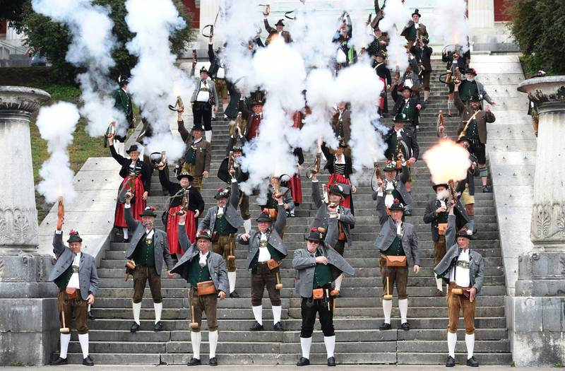 People wear local clothing as the fire guns during the traditional gun salute at the last day of the 'Oktoberfest' beer festival in Munich, Sunday, Oct. 7, 2018. (Felix Hoerhager/dpa via AP)