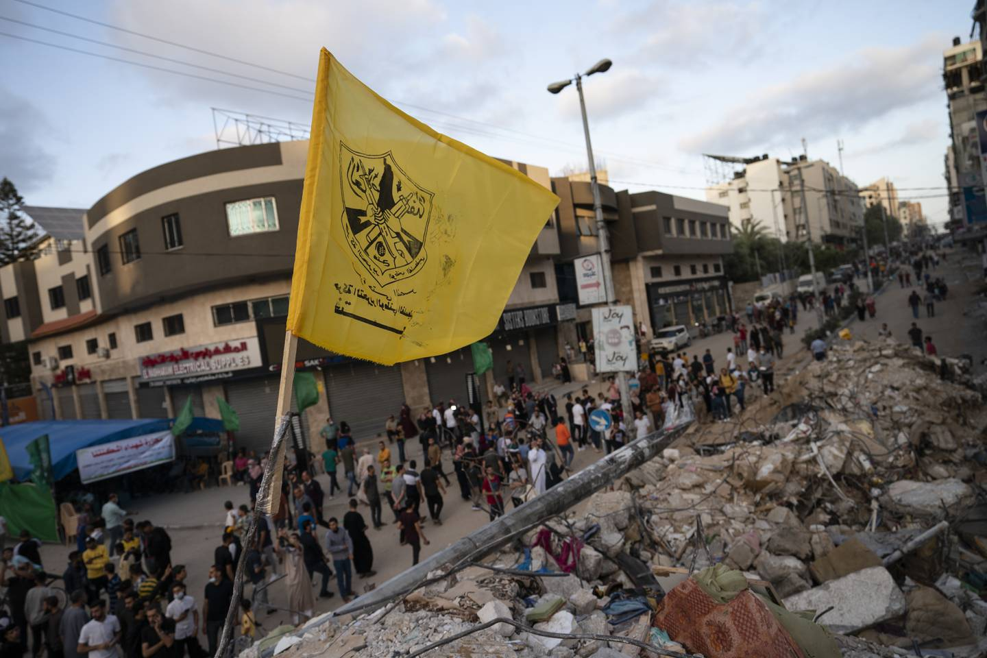 A Fatah flag is placed on top of a rubble heap beside a building previously destroyed by an air-strike following a cease-fire reached after an 11-day war between Gaza's Hamas rulers and Israel, in Gaza City, Friday, May 21, 2021. (AP Photo/John Minchillo)