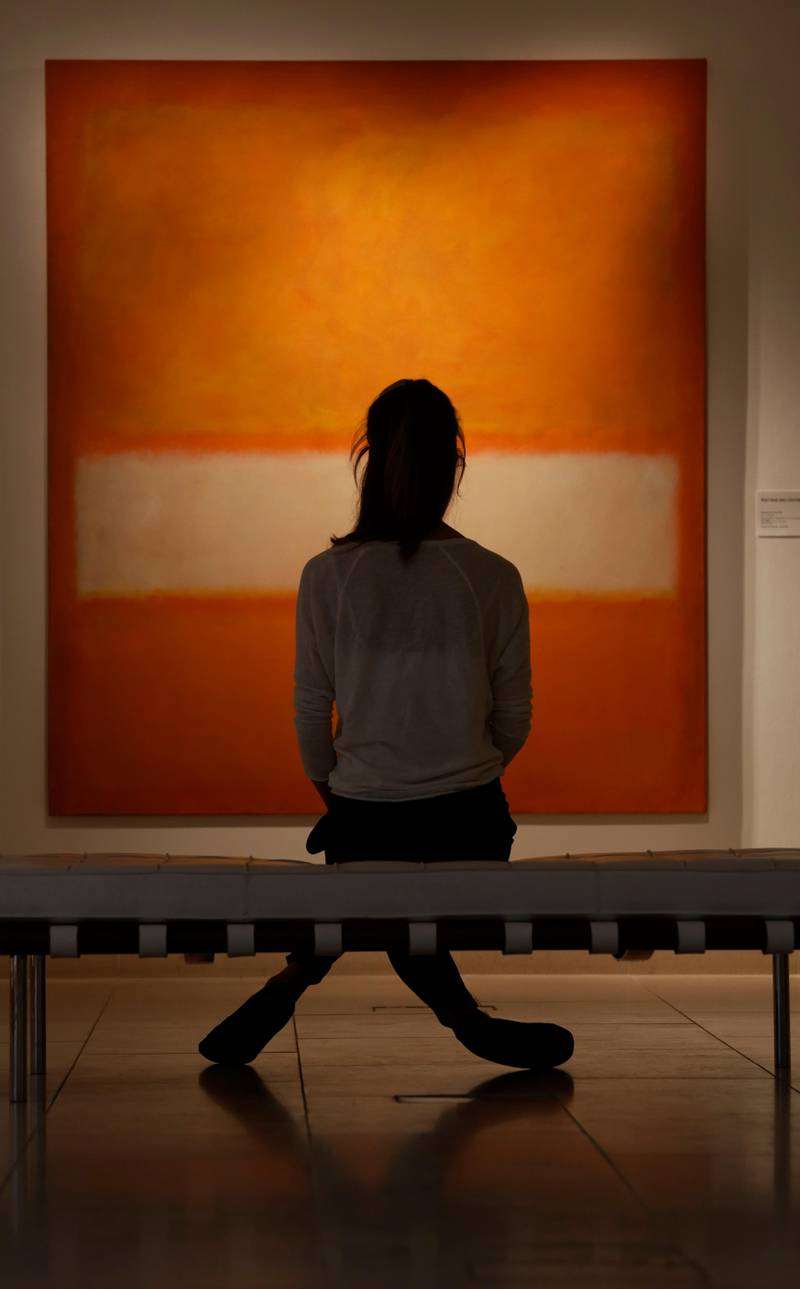 An auction house worker poses for photographers in front of an untitled oil on canvas 1957 painting by Mark Rothko in central London, Monday, Oct. 14, 2013. The artwork will be offered in auction at Christie's New York 'Evening Sale of Post-War and Contemporary Art' on Nov. 12, 2013. It is estimated to fetch some US$ 25-35 million (euro 18,4- 25,8 million). (AP Photo/Lefteris Pitarakis)
