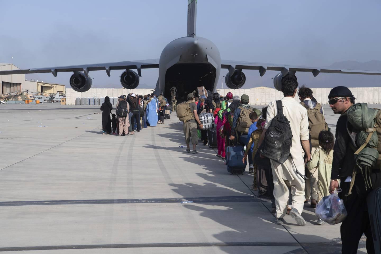 Afghanere i kø for å gå om bord i et amerikansk militærfly. Taliban lover ifølge USA å la amerikanere og afghanere i faresonen å forlate Afghanistan også etter 31. august. Foto: AP / NTB
