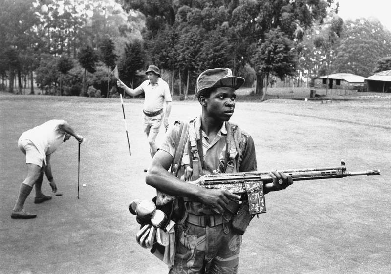 An armed guard provides both service and security on the golf course at the Hotel Leopard 1978 in Rhodesia. (AP Photo)